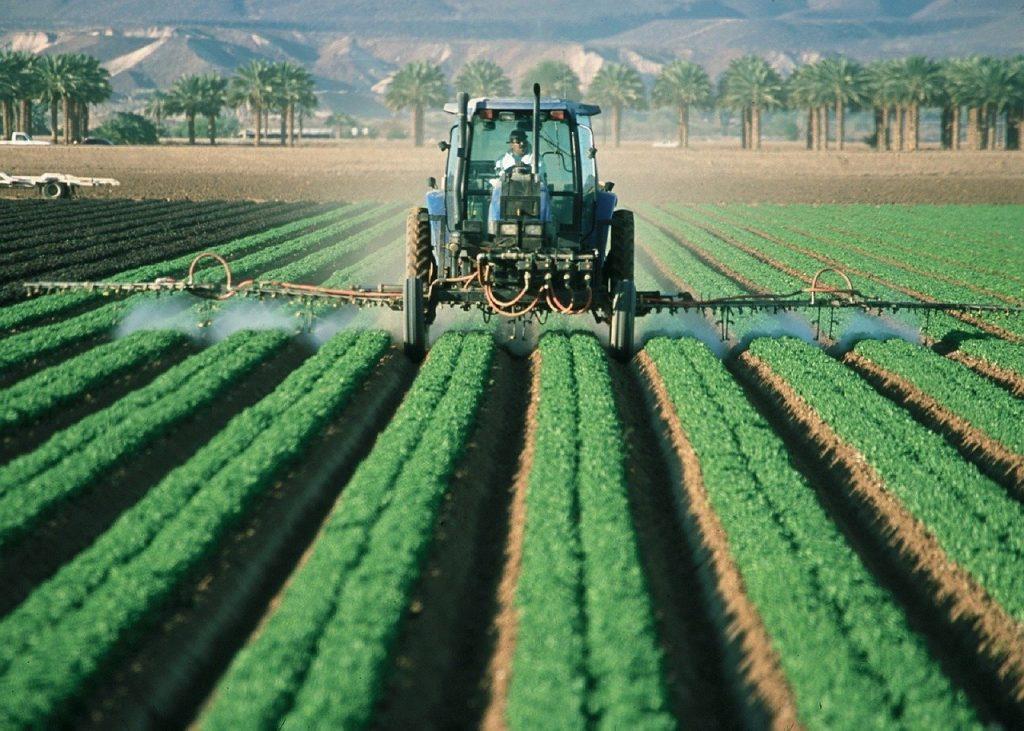 Épandage de pesticides en tracteur, à l'origine d'une pollution de l'environnement